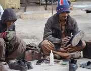 کوئٹہ: جناح روڈ پر دو محنت کش جوتے پالش کرنے میں مصروف ہیں۔