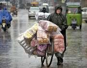 راولپنڈی: ایک معمر محنت کش بارش سے بچنے کے لیے برساتی پہنے پھیری لگا ..