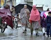 راولپنڈی: بارش سے بچنے کے لیے شہری چھتری تانے جا رہے ہیں۔