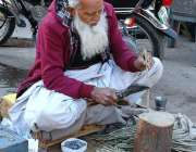 فیصل آباد: ایک معمر شخص فروخت کے لیے مسواکیں تیار کر رہا ہے۔