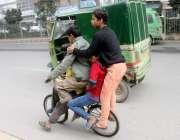 لاہور: کمسن بچے چھوٹی سائیکل پر سوار ہو کر فیروز پور روڈ سے گزر رہے ہیں۔
