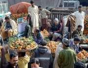 لاہور: فروٹ منڈی میں دکاندار آڑھتیوں سے کینوؤں کی خریداری کر رہے ہیں۔