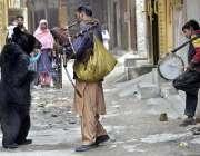 راولپنڈی: ایک تماش بین ریچھ کا تماشا دکھا کر لوگوں کو محضوض کر رہا ہے۔
