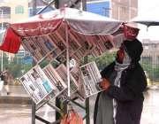 پشاور: ایک اخبار فروش سڑک کنارے بجلی کے کھمبے کے ساتھ اخبار لٹکائے فروخت ..