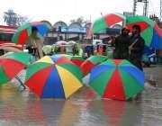 پشاور: ایک شخص بارش سے بچاؤ کے لیے چھتریاں فروخت کر رہا ہیوٴ۔