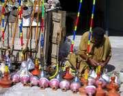فیصل آباد: ایک دکاندار حکے بنانے میں مصروف ہے۔