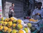 فیصل آباد: ریڑھی بان سڑک کنارے پپیتا فروخت کر رہا ہے۔
