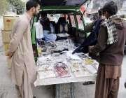 راولپنڈی: شہری روڈ کنارے کھڑی گاری سے تیار کپڑے خرید رہے ہیں۔