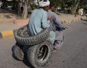 لاہور: ایک شخص خطر ناک انداز سے موٹر سائیکل پر ٹائر رکھے لیجا رہا ہے ..