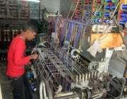 فیصل آباد: ایک کمسن محنت کش پاور لوم پر کام میں مصروف ہے۔
