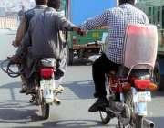 فیصل آباد: ایک موٹر سائیکل سوار دوسرے موٹر سائیکل سوار کی مدد کرتے ہوئے۔