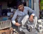 سرگودھا: ایک محنت کش اپنے ورکشاپ میں بیٹریاں مرمت کر رہا ہے۔