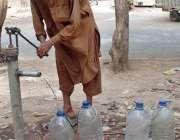 حیدر آباد: ایک شہری ہینڈ پمپ سے پینے کے لیے صاف پانی بوتلوں میں بھر رہا ..