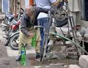 راولپنڈی: ایک معمر شخص ہینڈ پمپ سے پینے کے لیے صاف پانی بھر رہا ہے۔