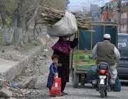 راولپنڈی: ایک خانہ بدوش خاتون اپنے بچے کے ہمراہ گھر کا چولہا جلانے کے ..