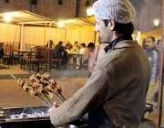 لاہور: فوڈ سٹریٹ میں ایک کاریگر باربی کیو تیار کررہا ہے۔