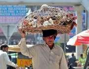 راولپنڈی: ایک محنت کش سر پر مرغیاں اٹھائے فروخت کے لیے جا رہا ہے۔