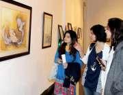 لاہور: نیشنل کالج آف آٹس میں لڑکیاں پینٹنگ کی نمائش دیکھ رہی ہیں۔