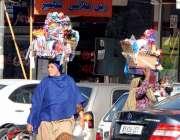 راولپنڈی: خاتون سرپر گھریلو اشیاء رکھے صدر روڈ پر فروخت کر رہی ہے۔