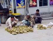 کوئٹہ: سورج گنج بازار میں ایک محنت کش زمن پر کیلے سجائے فروخت کر رہا ..