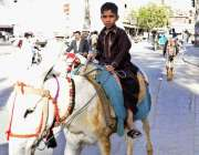 راولپنڈی: ایک کم عمر بچہ گدے پر بیٹھا مزدوری کے لیے جا رہا ہے۔