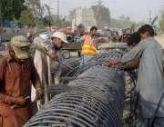 لاہور: مزدور چوبچہ انڈر پاس کے کے پلر کے لیے سریا باندھ رہے ہیں۔