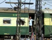 لاہور: ایک مسافر ٹرین کے دروازے میں کھڑا ہو کر سفر کر رہا ہے جو کسی ناخوشگوار ..