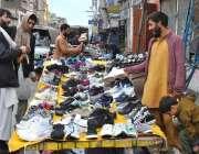 راولپنڈی: سڑک کنارے لگے سٹال سے شہری پرانے جوتے خرید رہے ہیں۔