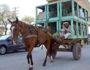 لاہور: ایک مزدور گدھا ریڑھی پر ائیرکولروں کی باڈیاں رکھے جا رہا ہے۔