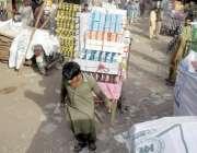 لاہور: مستی گیٹ بازار میں محنت کش بھاری سامان ہتھ ریڑھی پر رکھ کر لیجا ..
