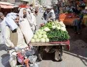 کوئٹہ: سبزی مارکیٹ میں شہری ایک ریڑھی بان سے سبزی خرید رہے ہیں۔