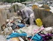 لاہور: ایک محنت کش کوڑے دان سے کار آمد اشیاء تلاش کر رہا ہے۔