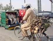 لاہور: ایک شخص گھر کا چولہا جلانے کے لیے لکڑیاں سائیکل کے پیچھے رکھ ..
