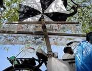 راولپنڈی: ایک محنت کش شاپر میں مچھلیاں سجائے درخت کے سائے تلے گاہکوں ..