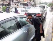 لاہور: شملہ پہاڑی چوک میں ایک بھیکاری بارش کے بعد ٹریفک سگنل پر بھیک ..