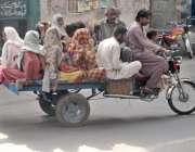لاہور: ایک خانہ بدوش موٹر سائیکل رکشے پر اپنے کنبے کو بٹھا کر لیجا رہا ..