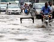 لاہور: شہر میں ہونیوالی بارش کے بعد ایک شاہراہ پر جمع پانی تالاب کی ..