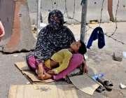 راولپنڈی: بھیک مانگنے والی ایک خاتون اپنی بچی کو گود میں لیے روڈ کنارے ..