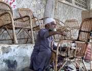 کراچی: ایک معمر محنت کش فٹ پاتھ پر بیٹھا کرسیاں بنا رہا ہے۔