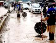 لاہور: شہر میں ہونیوالی بارش کے پانی کے نکاس کے لیے واسا کے اہلکار لکشمی ..