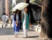 راولپنڈی: طالبات دھوپ سے بچنے کے لیے چھتری تانے جا رہی ہیں۔