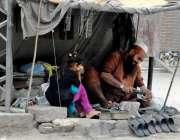 راولپنڈی: ایک بچی موچی سے جوتے سلائی کروا رہی ہے۔