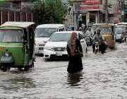 لاہور: ایک خاتون بارش کے بعد سی سی پی او آفس کے قریب جمع پانی میں سے گزر ..