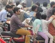 لاہور: مال روڈ پر ایک نوجوان اپنے پالتو کتے کو موٹر اسائیکل پر بیٹھا ..