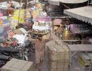 لاہور: مستی گیٹ بازار میں محنت کش بھاری سامان اپنے سروں پر اٹھا کر لیجا ..