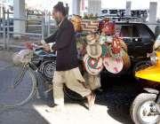 راولپنڈی: ایک معمر محنت کش سائیکل پر ہاتھ سے بنائی گئی اشیاء رکھے فروخت ..