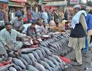 لاہور: ایک دکاندار مچھلی فروخت کر رہا ہے۔