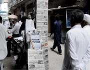 راولپنڈی: اخبار فروش نے اخبار سجا رکھے ہیں جبکہ شہری کھڑے اخبار کا مطالعہ ..