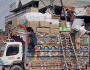 لاہور: سرکلر روڈ پر مزدور ٹرک پر سامان لوڈ کررہے ہیں۔