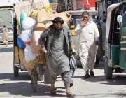 کوئٹہ: لیاقت بازار میں ایک معمر محنت کش بھاری سامان ہتھ ریڑھی پر لادھے ..